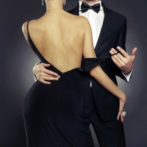 Man in tuxedo, lady in cocktail dress with her back to the onlooker