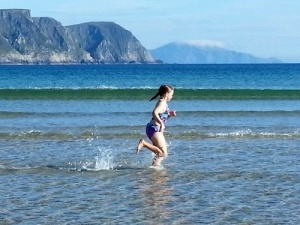 Photo of girl running in the water at the beach